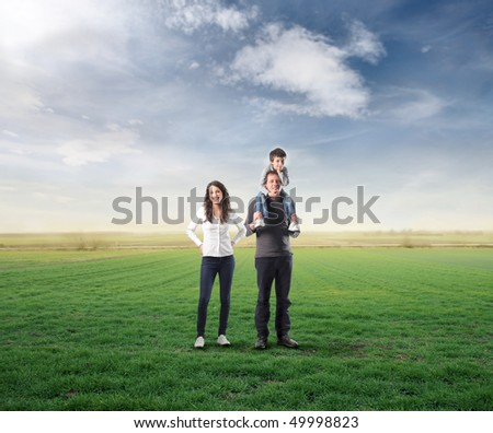 Smiling family standing on a green meadow - stock photo