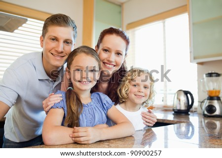 Smiling family standing together behind the kitchen counter - stock photo