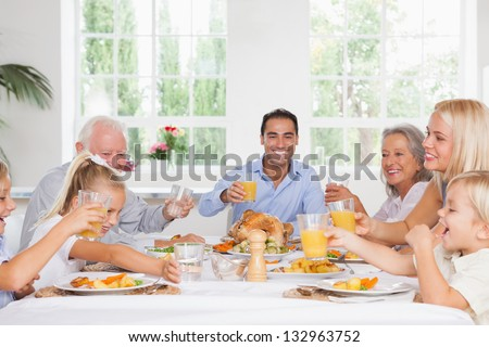 Smiling family toasting at thanksgiving at the dinner table - stock photo