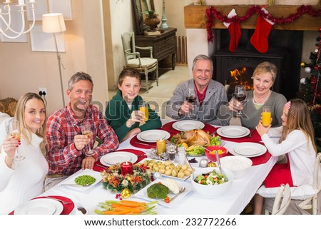 Smiling family toasting to camera during christmas dinner at home in the living room - stock photo