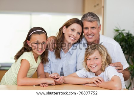 Smiling family together behind table