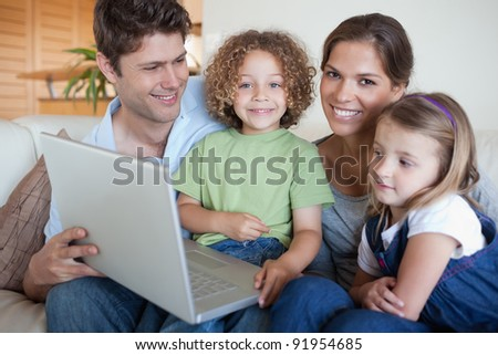Smiling family using a laptop in their living room - stock photo