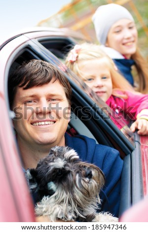 smiling family with a dog in the car - stock photo