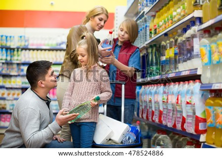 Smiling family with children purchasing bottle of sparkling water in store. Selective focus
