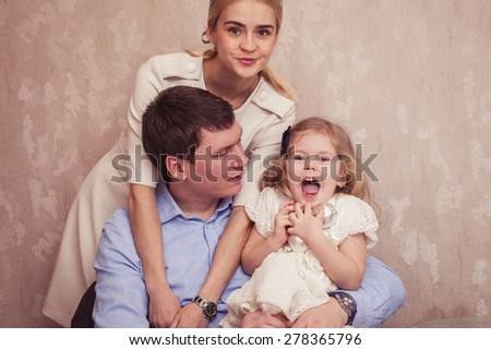 Smiling family with daughter playing together in living room - stock photo