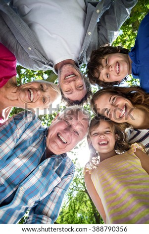 Smiling family with their heads in a circle in the garden - stock photo