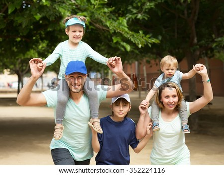 Smiling family with three kids having city tour in summer day - stock photo