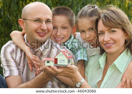 smiling family with two children is keeping wendy house in their hands and looking at camera. focus on boy's face. wendy house in out of focus. - stock photo