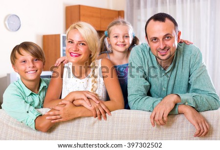 Smiling family with two kids on couch indoors - stock photo