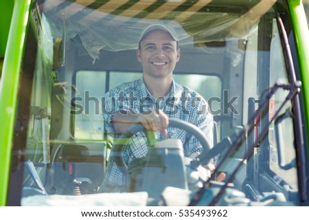 Smiling farmer driving a tractor in his field