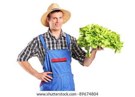 Smiling farmer holding a lettuce in his hand isolated on white background - stock photo