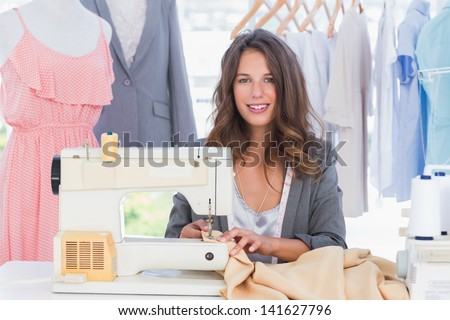 Smiling fashion designer using sewing machine and sitting behind her desk - stock photo