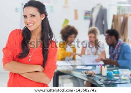 Smiling fashion designer with arms crossed standing in front of her creative team - stock photo