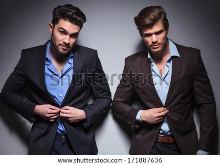 smiling fashion men buttoning their coats and posing for the camera - stock photo