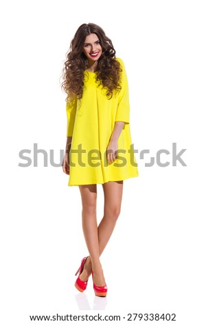 Smiling fashion model posing in red high heels and yellow mini dress. Full length studio shot isolated on white. - stock photo