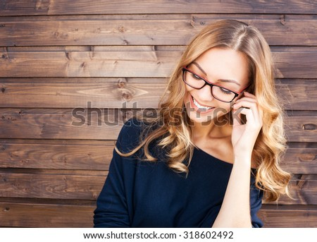 Smiling fashionable blonde laughs outdoors on wooden background