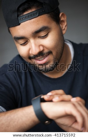 Smiling fashionable young black boy using his trendy smart watch.Modern gadget that lets you always stay connected to internet,social media from everywhere. - stock photo