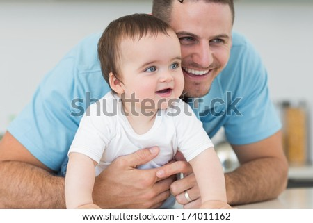 Smiling father and baby boy lying on floor at home - stock photo