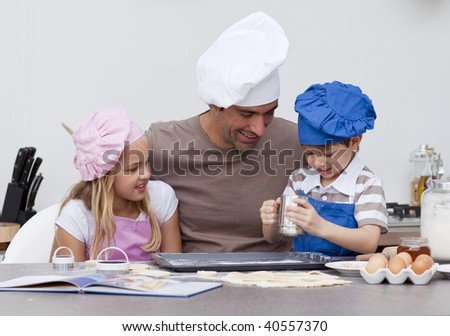 Smiling father and children baking in the kitchen - stock photo