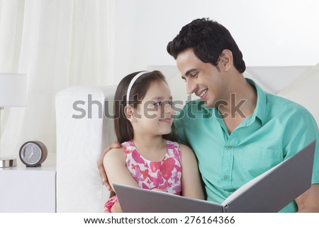 Smiling father and daughter with file looking at each other - stock photo