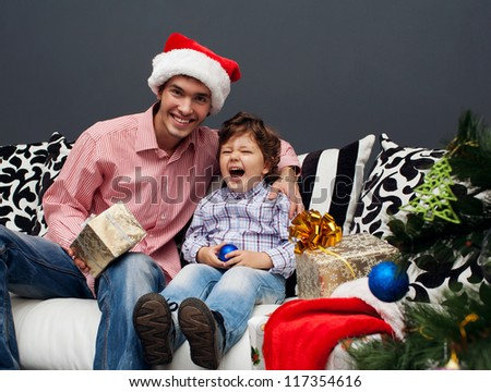 Smiling father and his son opening Christmas presents in the living-room