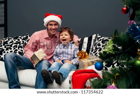 Smiling father and his son opening Christmas presents in the living-room - stock photo