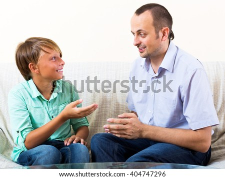 Smiling father and young son discussing something interesting indoors at home - stock photo