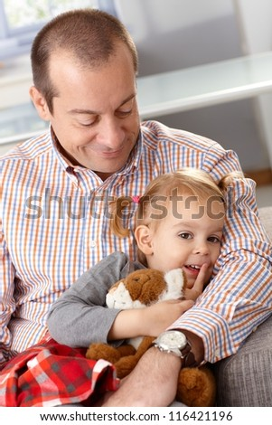 Smiling father hugging little daughter. - stock photo