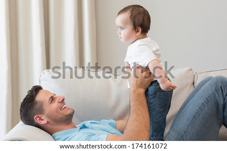 Smiling father playing with baby in living room - stock photo