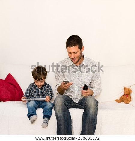 Smiling father playing with his phone while son is playing with tablet on a white sofa with a red pillow and a bear toy - stock photo
