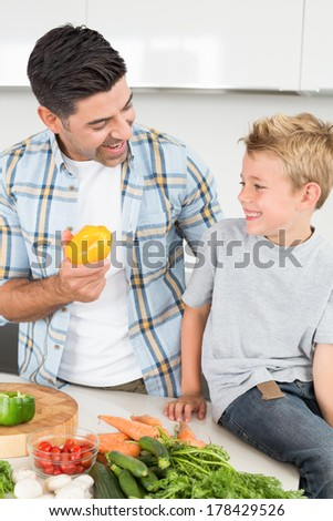 Smiling father showing his son a yellow pepper at home in kitchen - stock photo