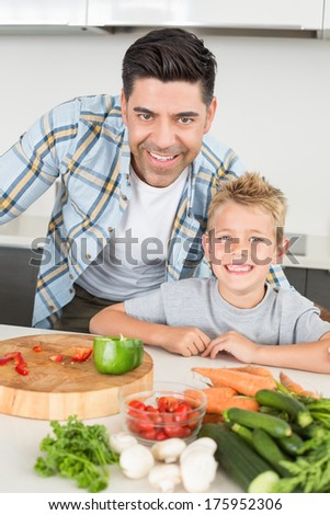 Smiling father showing his son how to prepare vegetables at home in kitchen - stock photo