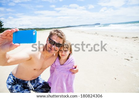Smiling father taking selfie photograph with young daughter at beach using mobile phone - stock photo