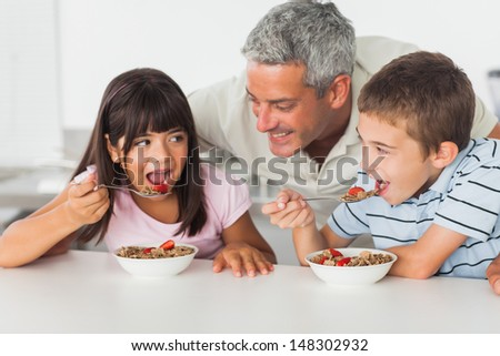 Smiling father talking with his children during their breakfast in kitchen - stock photo