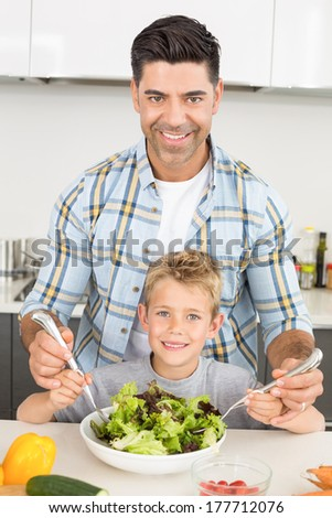 Smiling father tossing salad with his cute son at home in kitchen - stock photo