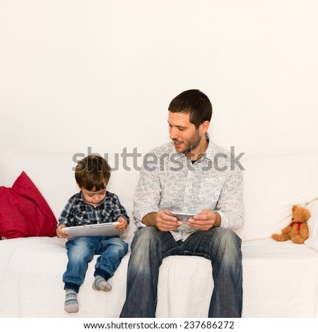 Smiling father watching his son playing with tablet on a white sofa with a red pillow and a bear toy - stock photo