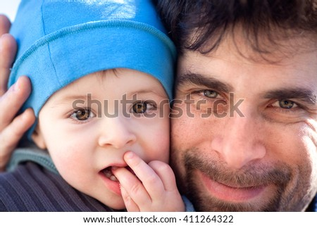 smiling father with beard hug his son with blue hat portrait - stock photo