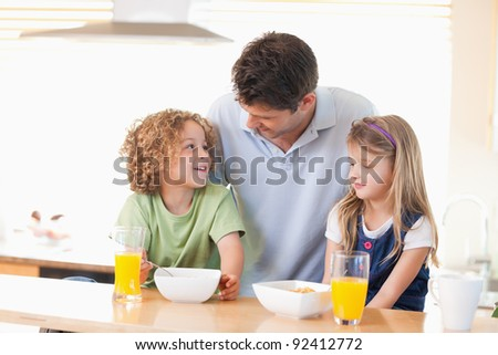 Smiling father with his children having breakfast in their kitchen - stock photo