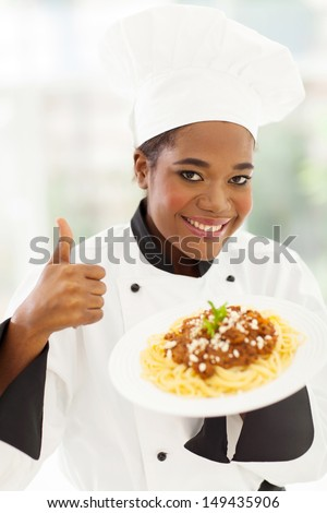 smiling female african american chef giving thumb up - stock photo