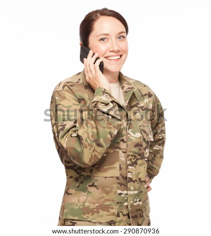 Smiling female Army soldier wearing multicam camouflage on her mobile cell phone. - stock photo