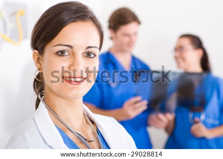 smiling female beautiful doctor in hospital, background is her colleagues - stock photo