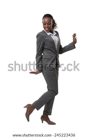 Smiling female businesswoman dancing and her legs crossed against a white background - stock photo