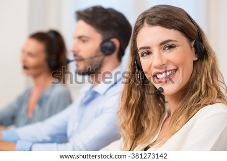 Smiling female call centre operator doing her job with a headset while looking at camera. Portrait of happy woman in a callcenter smiling and working. Portrait of happy smiling support phone operator. - stock photo