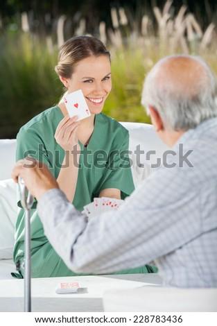 Smiling female caretaker showing ace card to senior man at nursing home - stock photo