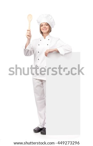 smiling female chef, cook or baker holding spoon and standing next to the banner with empty copy space for you text isolated on white background. advertisement blank board. your text here - stock photo