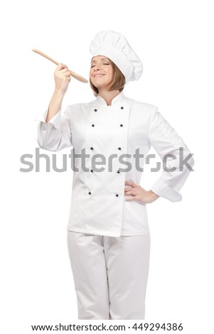 smiling female chef, cook or baker with wooden spoon enjoying food isolated on white background. cooking and food concept