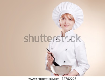 Smiling female chef with bowl and mixer in her hands on beige background - stock photo
