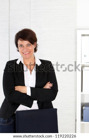 Smiling female corporate executive standing behind her office chair with her arms folded