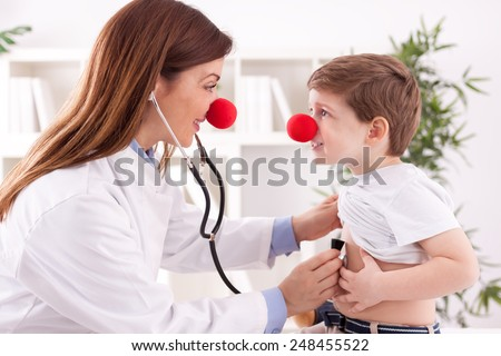 Smiling female doctor clown listen patient heart  - stock photo