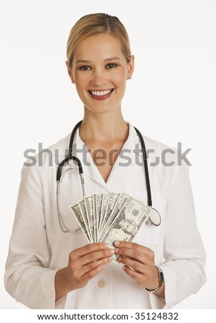 smiling female doctor fanning out one hundred and twenty dollar bills - stock photo
